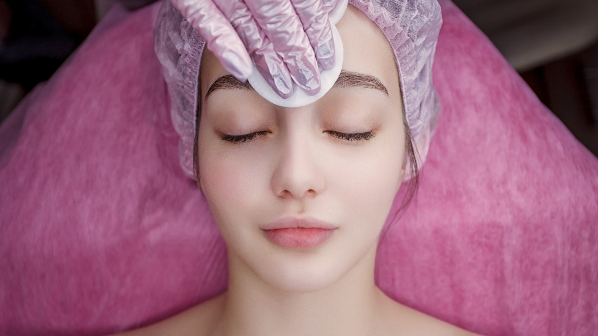 Beautician makes cleansing facial skin girl. Beauty treatment. Cosmetology. Cosmetologist hands cleanse the skin. Facial skin care. Smiling girl procedure. Visiting cosmetology clinic.